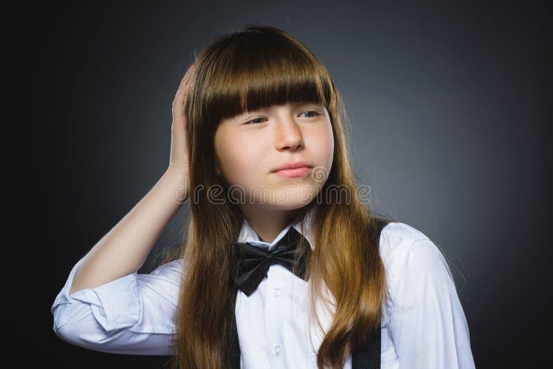 Девушка крупного плана заботливая с рукой на голове изолированной на сером цвете стоковое изображение rf