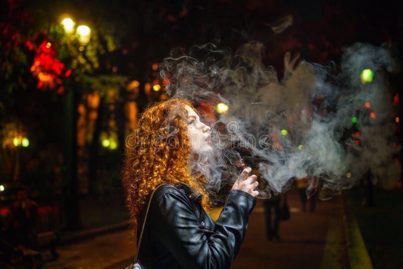 Девушка курит электронную сигарету стоковое фото rf