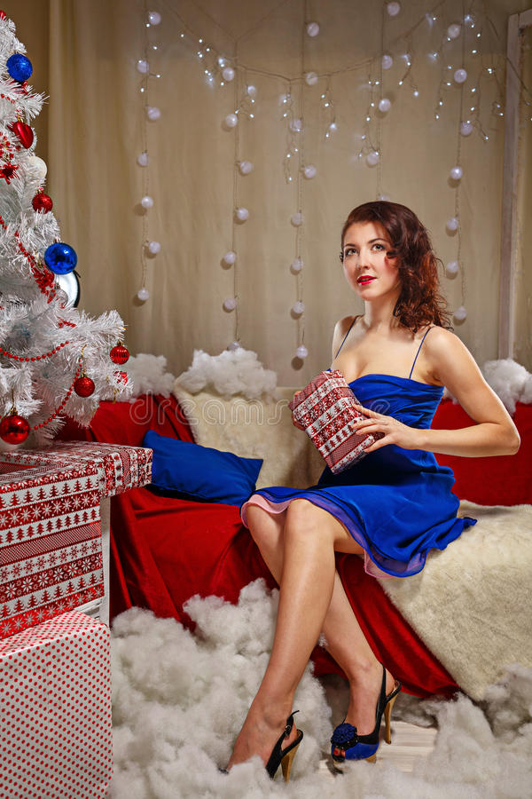 Девушка кладет вне подарки около рождественской елки стоковое изображение rf