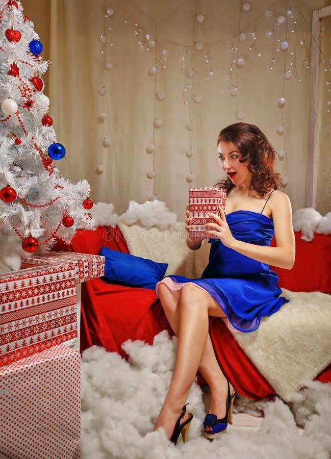 Девушка кладет вне подарки около рождественской елки стоковая фотография