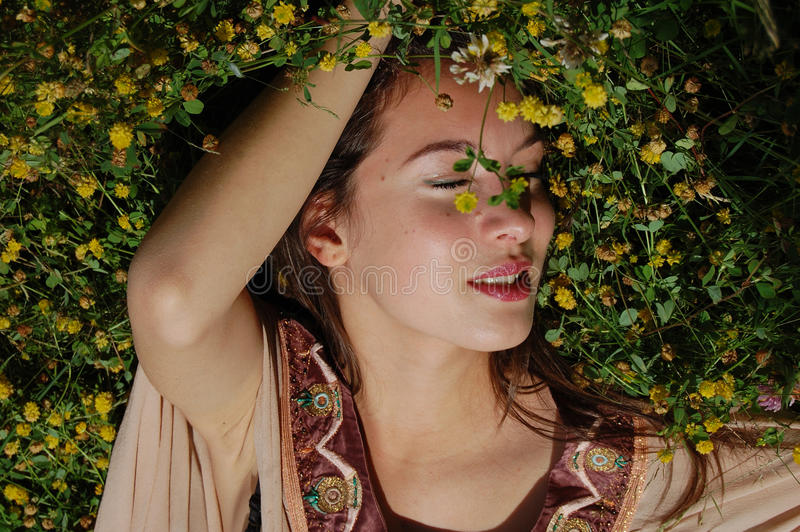 Девушка кладя в траву наслаждаясь летним временем стоковые фото