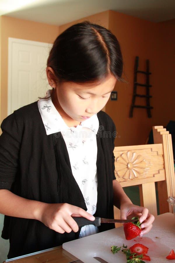 Девушка клубник вырезывания смотря вниз стоковые изображения