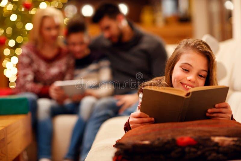 Девушка лежа и наслаждаясь в хорошей книге детей для рождества стоковое изображение rf