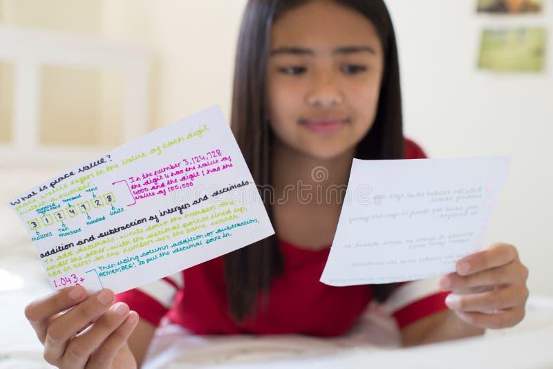 Девушка лежа на кровати используя написанные карточки исследования для того чтобы помочь с Revisio стоковое фото rf