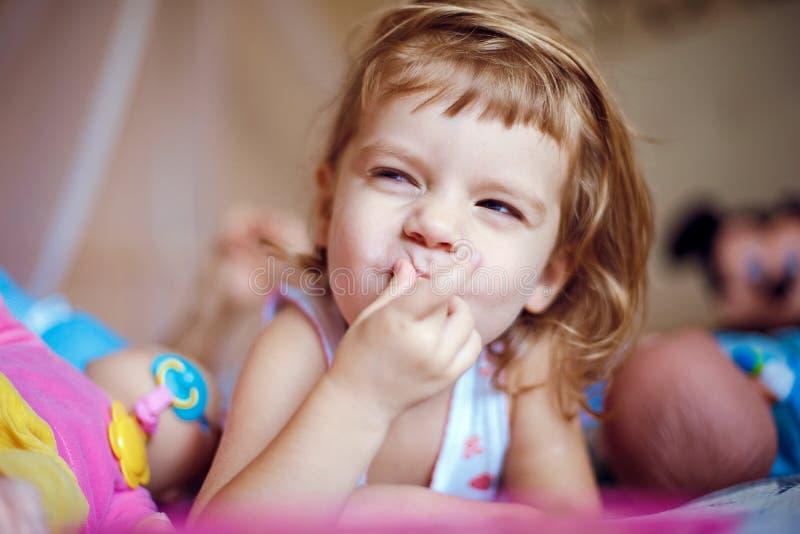 Девушка лежа с пальцами в рте стоковые изображения