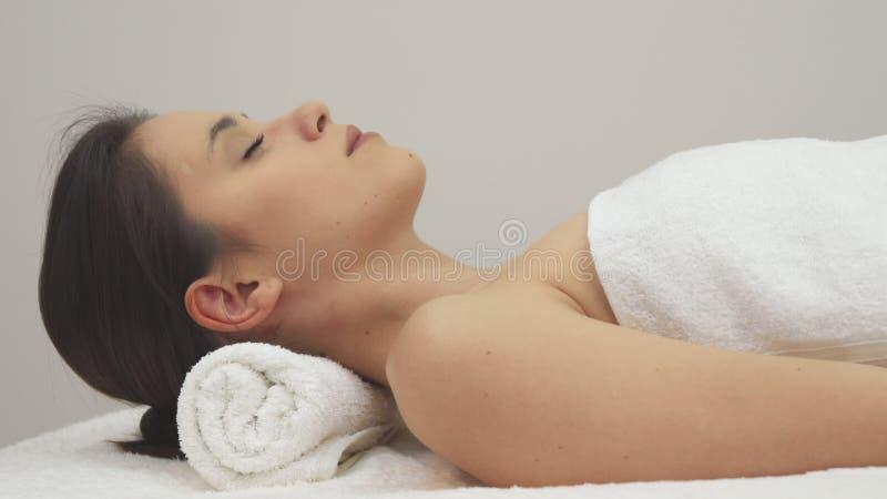 Девушка лежит на ей назад на таблице массажа стоковая фотография