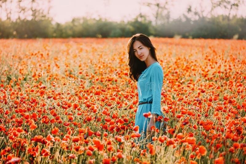Девушка лета красивая идя в красное поле цветка мака стоковое изображение rf