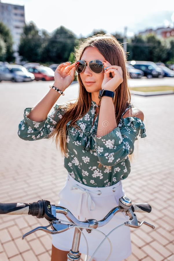 Девушка летом в стойках города с велосипедом в городе Носит солнечные очки Зеленая блузка и белые шорты юбки стоковое изображение rf