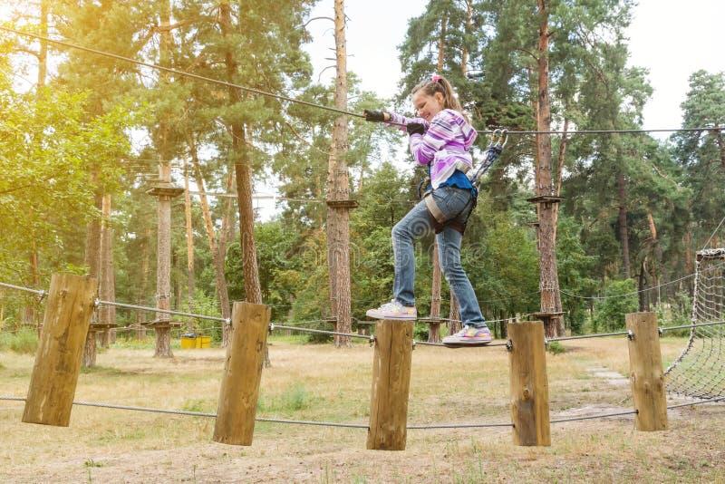 Девушка 10 лет в парке натянутой проволоки приключения взбираясь, активный образ жизни детей стоковое фото rf