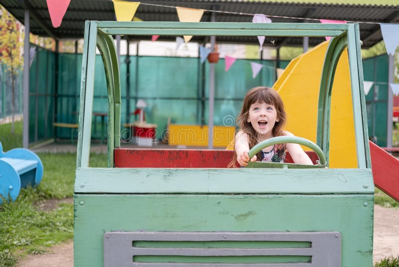Девушка 5 лет потехи портретируя водителя деревянного автомобиля на спортивной площадке стоковое фото rf