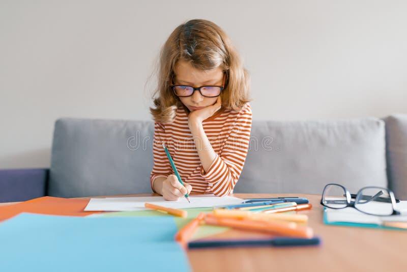 Девушка 8 лет сидит на софе дома рисует пишет с карандашем на бумаге Блондинка ребенка со стеклами изучая дома стоковое изображение rf