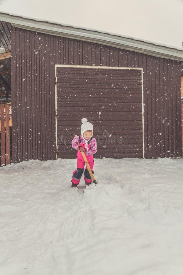 Девушка, лопаткоулавливатель младенца большой извлекает снег из пути в задворк на гараже стоковая фотография rf