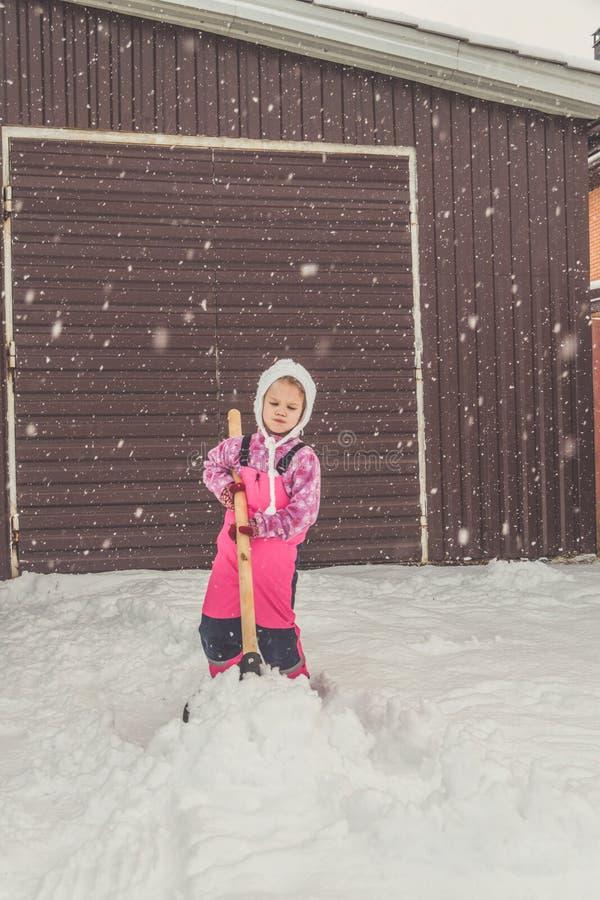 Девушка, лопаткоулавливатель младенца большой извлекает снег из пути в задворк на гараже стоковая фотография