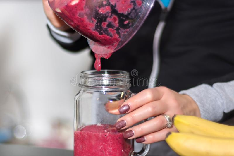 Девушка льет красный smoothie ягоды от blender для того чтобы раздражать стекло стоковое фото rf
