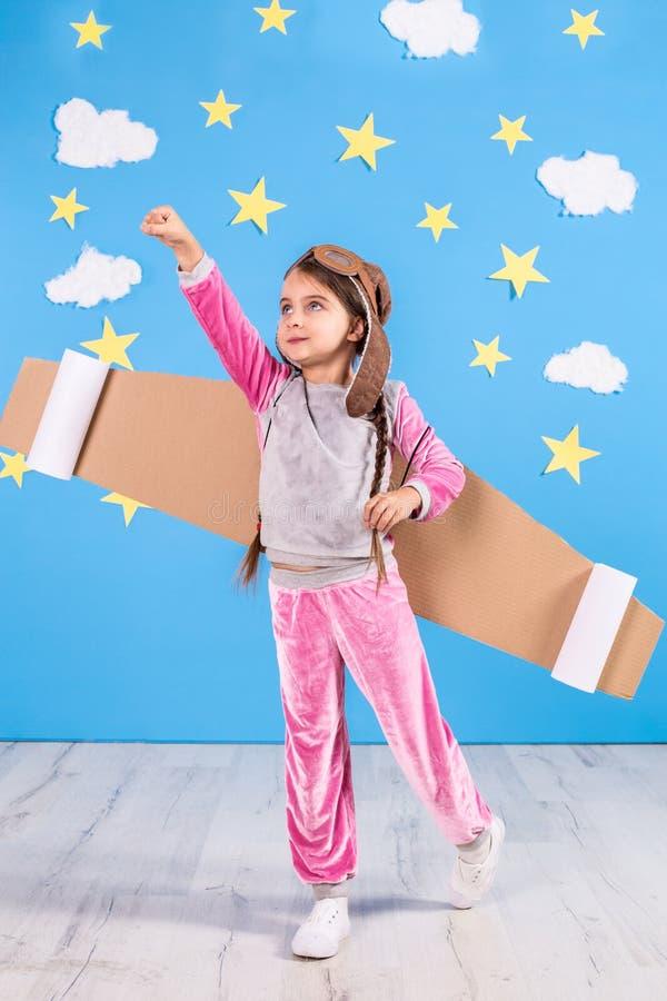 Девушка маленького ребенка в костюме астронавта играющ и мечтающ быть космонавтом стоковые фото