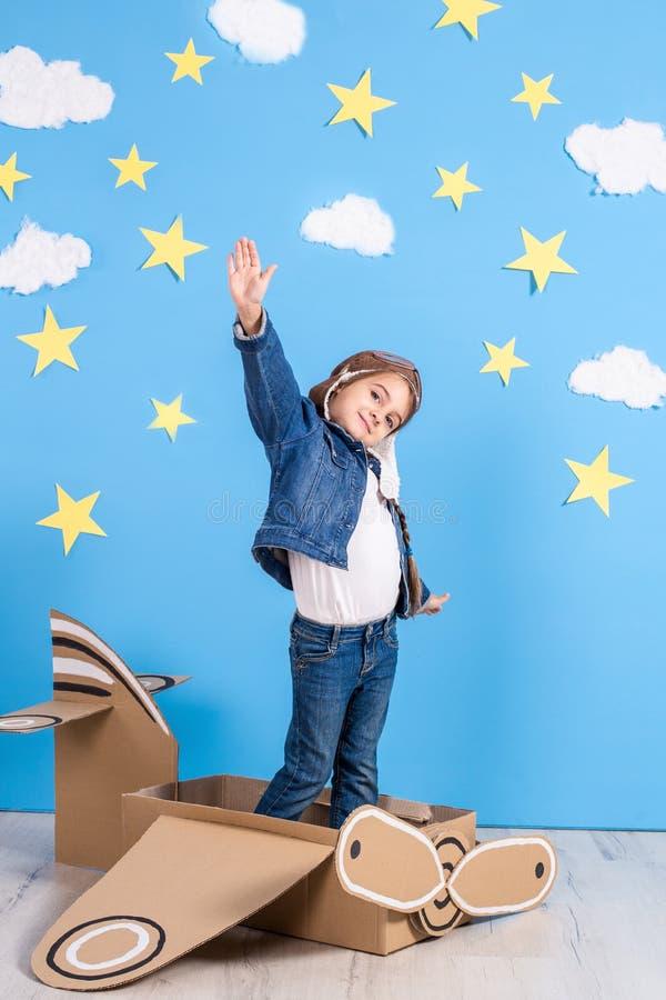Девушка маленького ребенка в пилотном костюме ` s играющ и мечтающ летания над облаками стоковые изображения rf