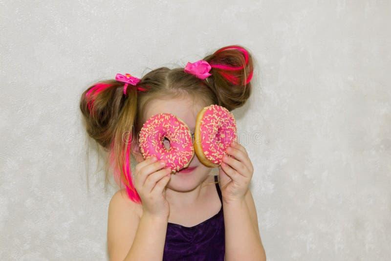 Девушка маленького ребенка плещется и играет с 2 свежими donuts перед едой Ребенок держит donuts около его глаз и взгляды через стоковое изображение rf