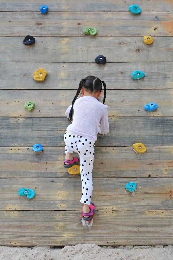 Девушка маленького ребенка пробуя на свободный взбираться на стене спортивной площадки деревянной outdoors стоковое фото