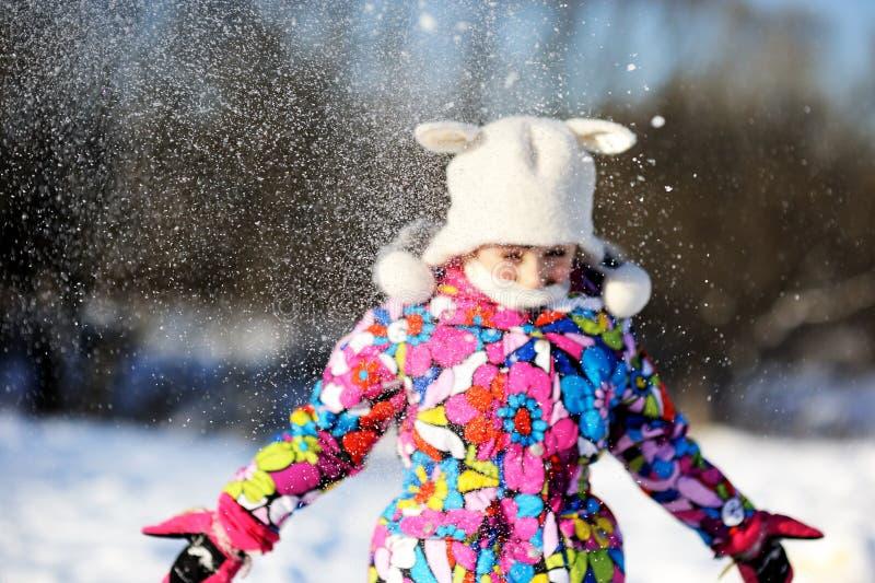 Девушка малыша в цветастом snowsuit играет в снежке стоковая фотография