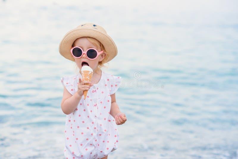 Девушка малыша одетая в одеждах лета и розовых стойках солнечных очков на пляже ест с мороженым большего удовольствия белым стоковое фото rf