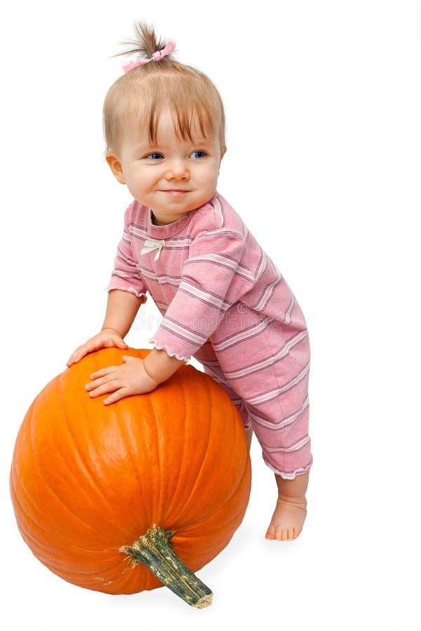 Девушка малыша полагается на тыкве стоковые изображения rf