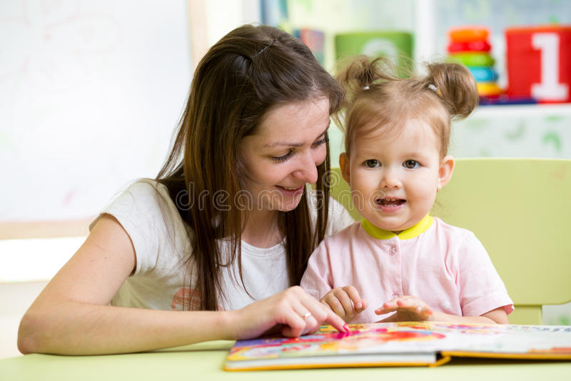 Девушка матери и ребенка прочитала книгу дома стоковое фото rf
