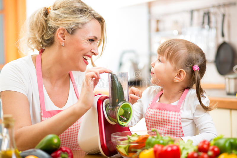 Девушка матери и ребенк подготавливая здоровую еду стоковые изображения rf