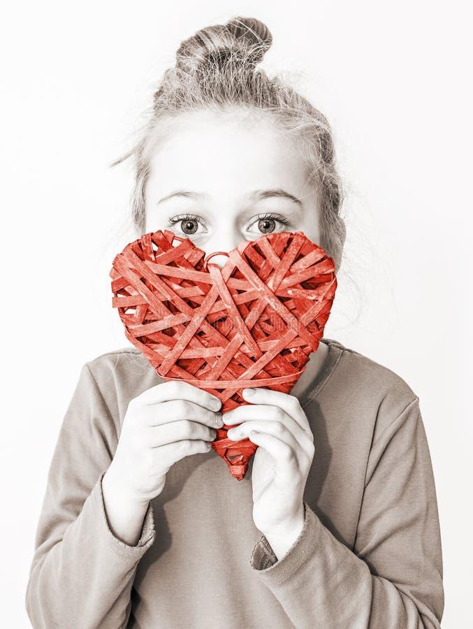 Девушка маленького ребенка держа красный символ сердца - полюбите концепцию стоковая фотография rf