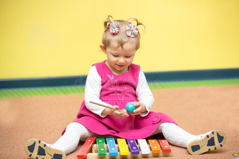 Девушка маленького ребенка играя в детском саде в классе Montessori стоковая фотография rf
