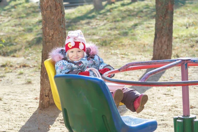 Девушка малыша играя на карусели или весел-идет стоковые фото