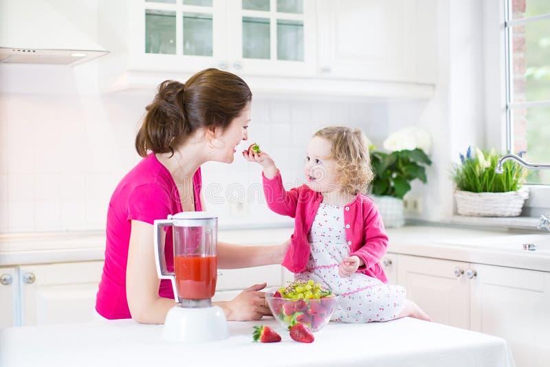 Download Девушка малыша и прелестная мать делая свежую клубнику Стоковое Изображение - изображение насчитывающей нутряно, еда: 41657093