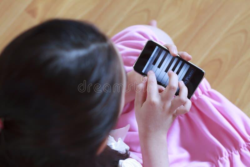девушка меньший играть рояля телефона стоковые изображения rf