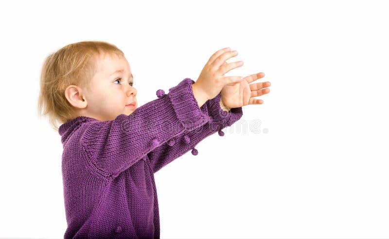 девушка младенца милая достигая что-то стоковое фото