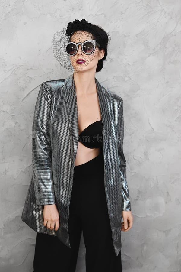 Девушка модного полу-нагого брюнета модельная с ярким макияжем и со стильной шляпой в unbuttoned серебряной куртке, внутри стоковая фотография rf