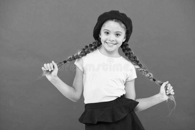Девушка моды ребенк маленькая милая представляя с длинными оплетками и предпосылкой шляпы красной E Модный аксессуар берета стоковые изображения