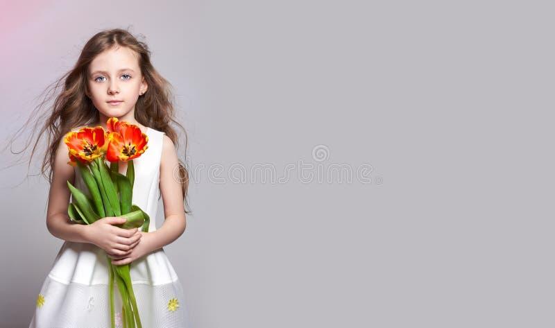 Девушка моды рыжеволосая с тюльпанами в руках Фото студии на предпосылке покрашенной светом День рождения, праздник, день матерей стоковое изображение