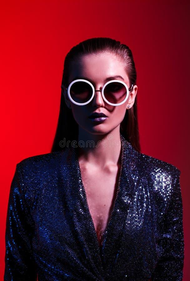 Девушка моды с длинными волосами и круглыми солнечными очками в черном сияющем платье представляет в неоновом свете в студии стоковая фотография