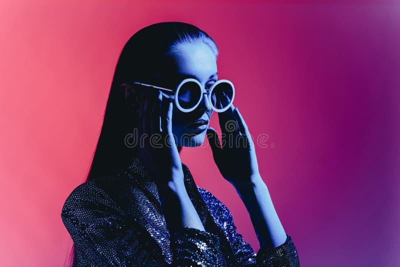 Девушка моды с длинными волосами и круглыми солнечными очками в черном сияющем платье представляет в неоновом свете в студии стоковое изображение
