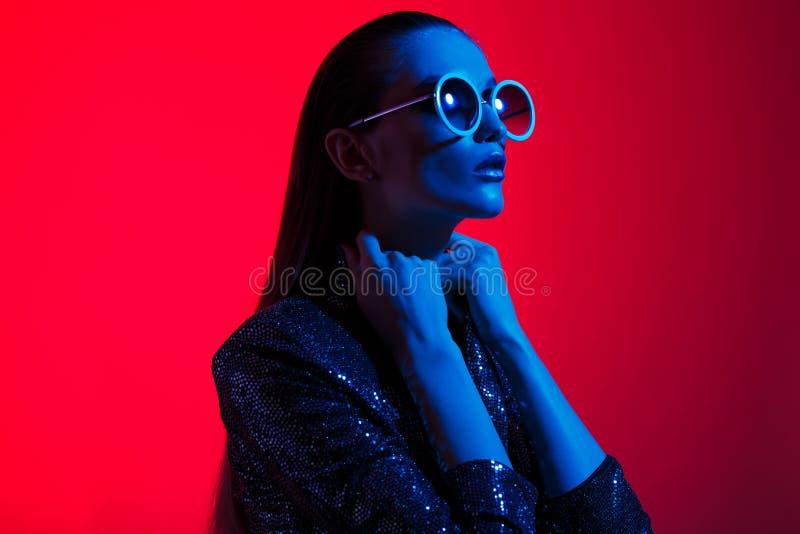 Девушка моды с длинными волосами и круглыми солнечными очками в черном сияющем платье представляет в неоновом свете в студии стоковое фото rf
