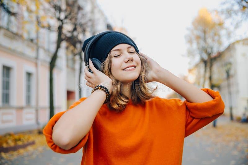 Девушка молодого милого битника предназначенная для подростков в музыке черной шляпы слушая через наушники на улице осени стоковое фото