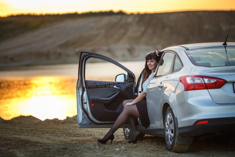 Девушка молодого счастливого красивого большого размера модельная сидеть в ее автомобиле на заходе солнца около реки бизнес-леди  стоковая фотография rf