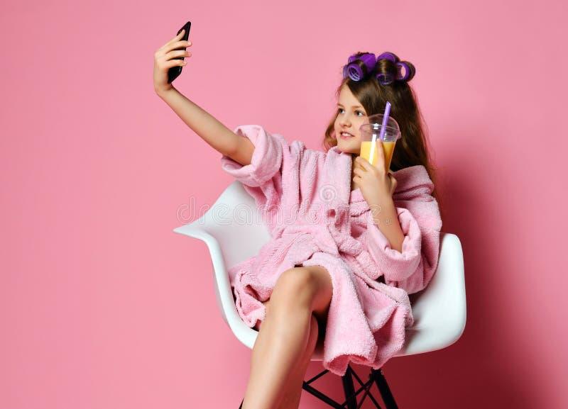 Девушка молодой дамы предназначенная для подростков в купальном халате и с волосами в curlers выпивает сок smoothie свежий и имет стоковая фотография