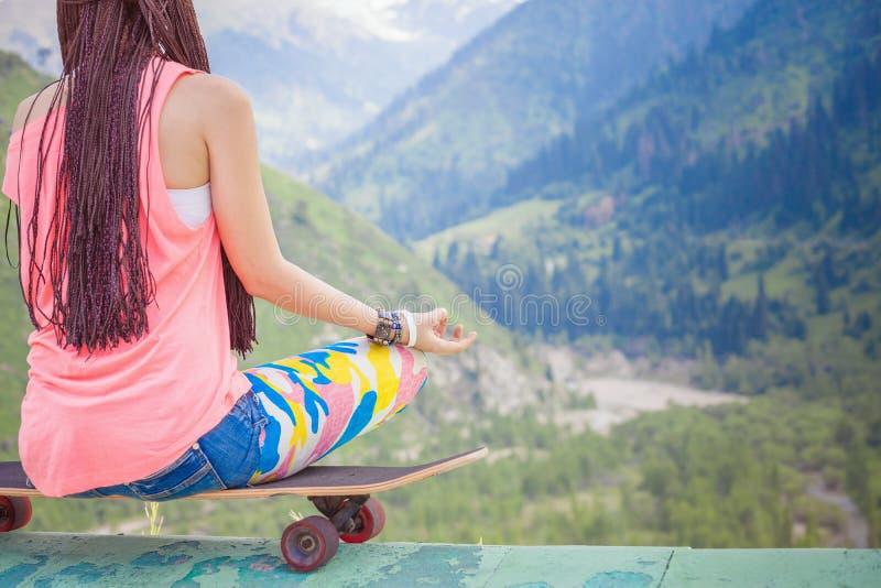 Девушка моды битника делая йогу, ослабляя на скейтборде на горе стоковое изображение