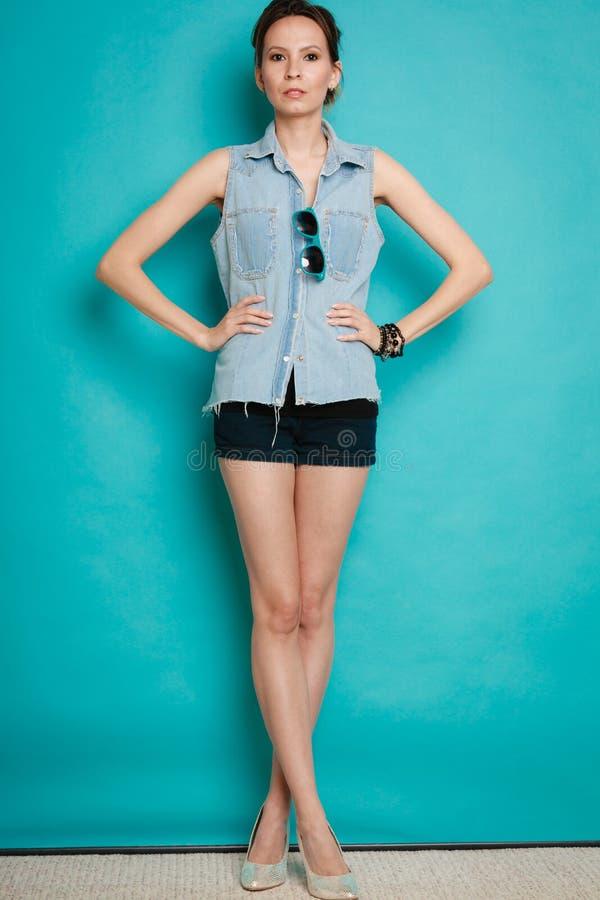 Девушка моды лета в шортах рубашки джинсов и высоких пятках стоковое изображение rf