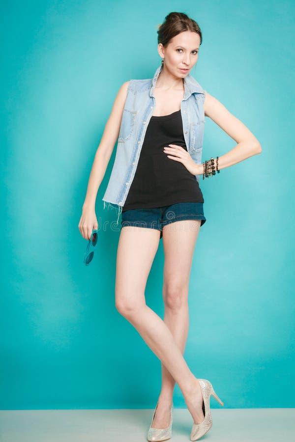 Девушка моды лета в шортах рубашки джинсов и высоких пятках стоковые фотографии rf