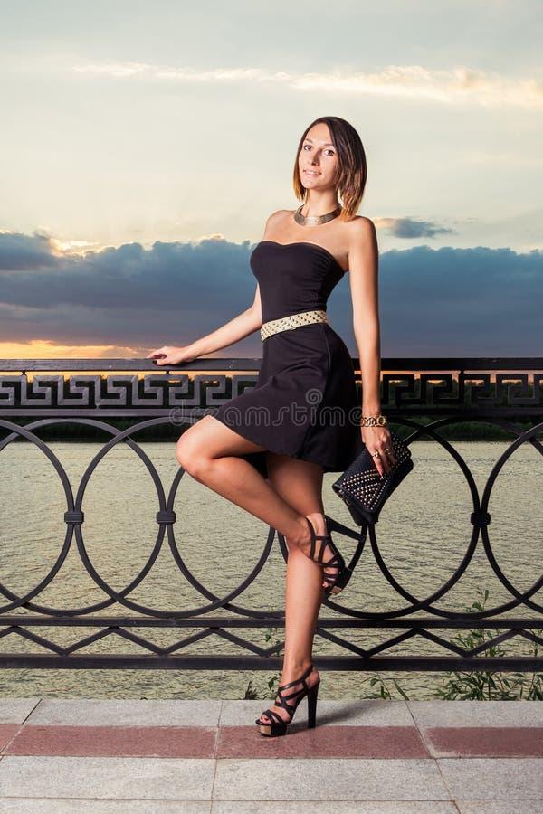 Девушка моды с стоит на одной ноге с ей стоковая фотография