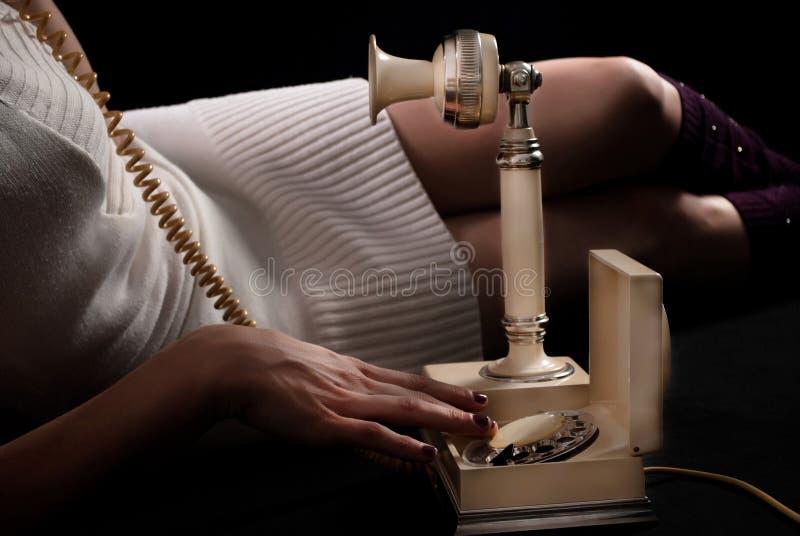 Девушка набирая и говоря на очень старом телефоне и лож на поле стоковое изображение