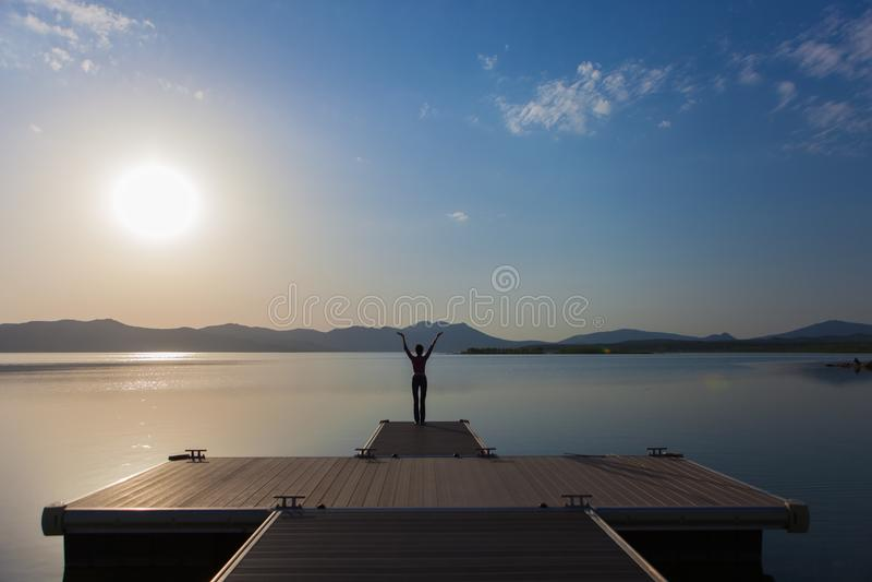Девушка наблюдая заход солнца на озере стоковые изображения