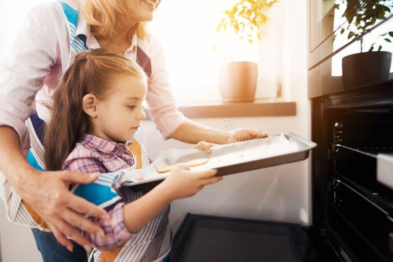 Девушка нагружает печенья в печи Ее бабушка помогает ей стоковое изображение