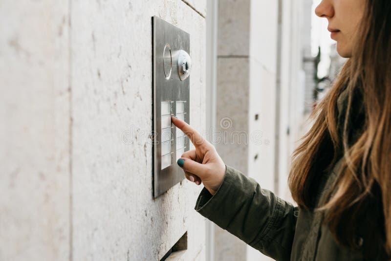 Девушка нажимает кнопку doorphone или вызывает внутренную связь стоковое фото rf